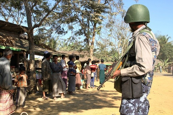 A Myanmar border guard policeman stand near a group of Rohingya Muslims in front of their homes in a village are seen during a government-organized visit for journalists in Buthidaung townships in the restive Rakhine state on January 25, 2019. (Photo by Richard SARGENT / AFP)