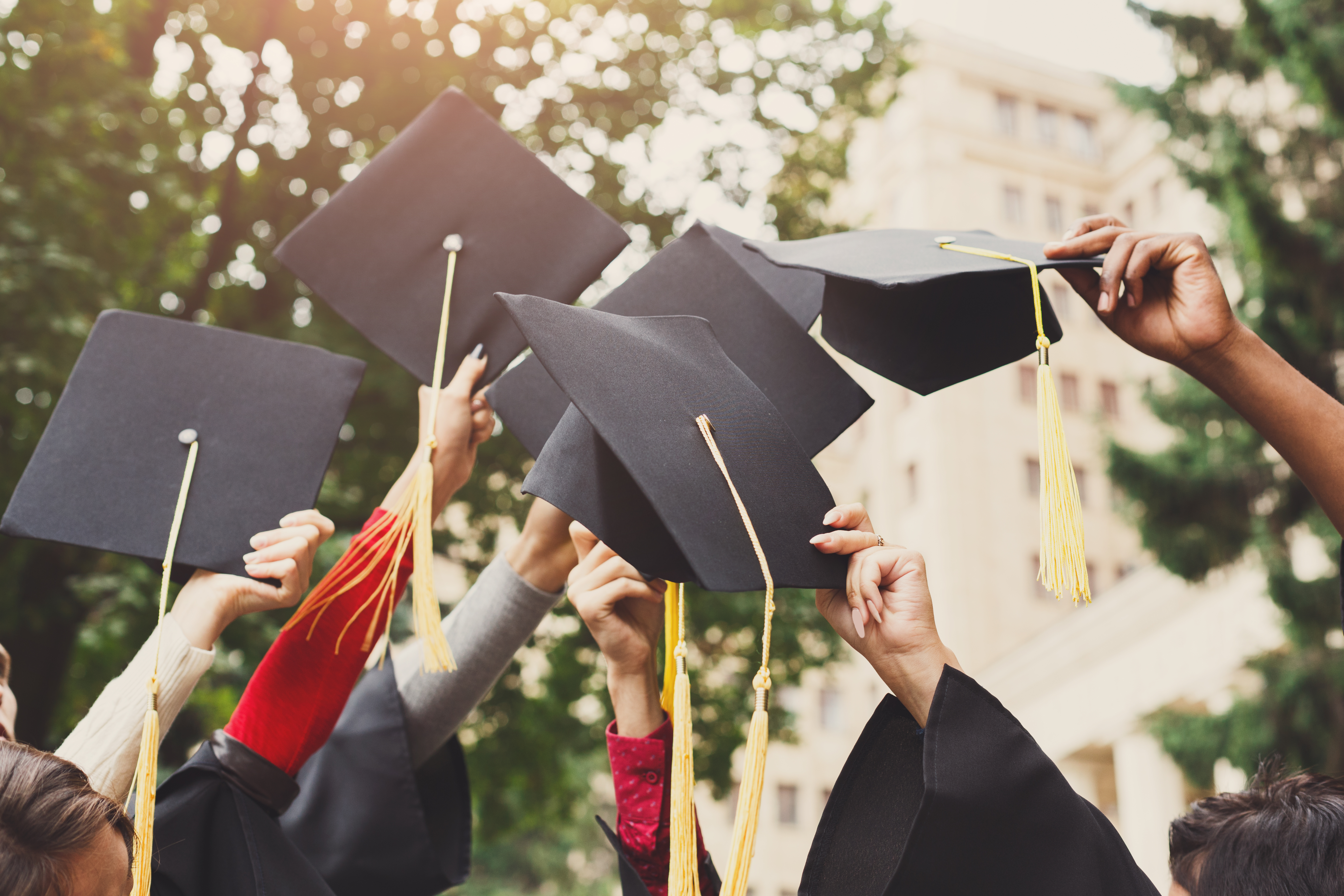 A group of multietnic students celebrating their graduation by throwing caps in the air closeup. Education, qualification and gown concept.