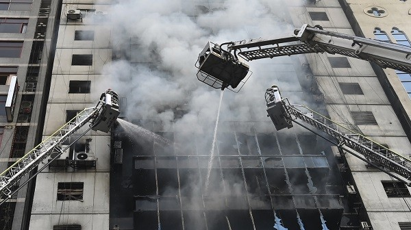 Bangladeshi firefighters on ladders work to extinguish a blaze in an office building in Dhaka on March 28, 2019 (Photo: MUNIR UZ ZAMAN/AFP/Getty Images).