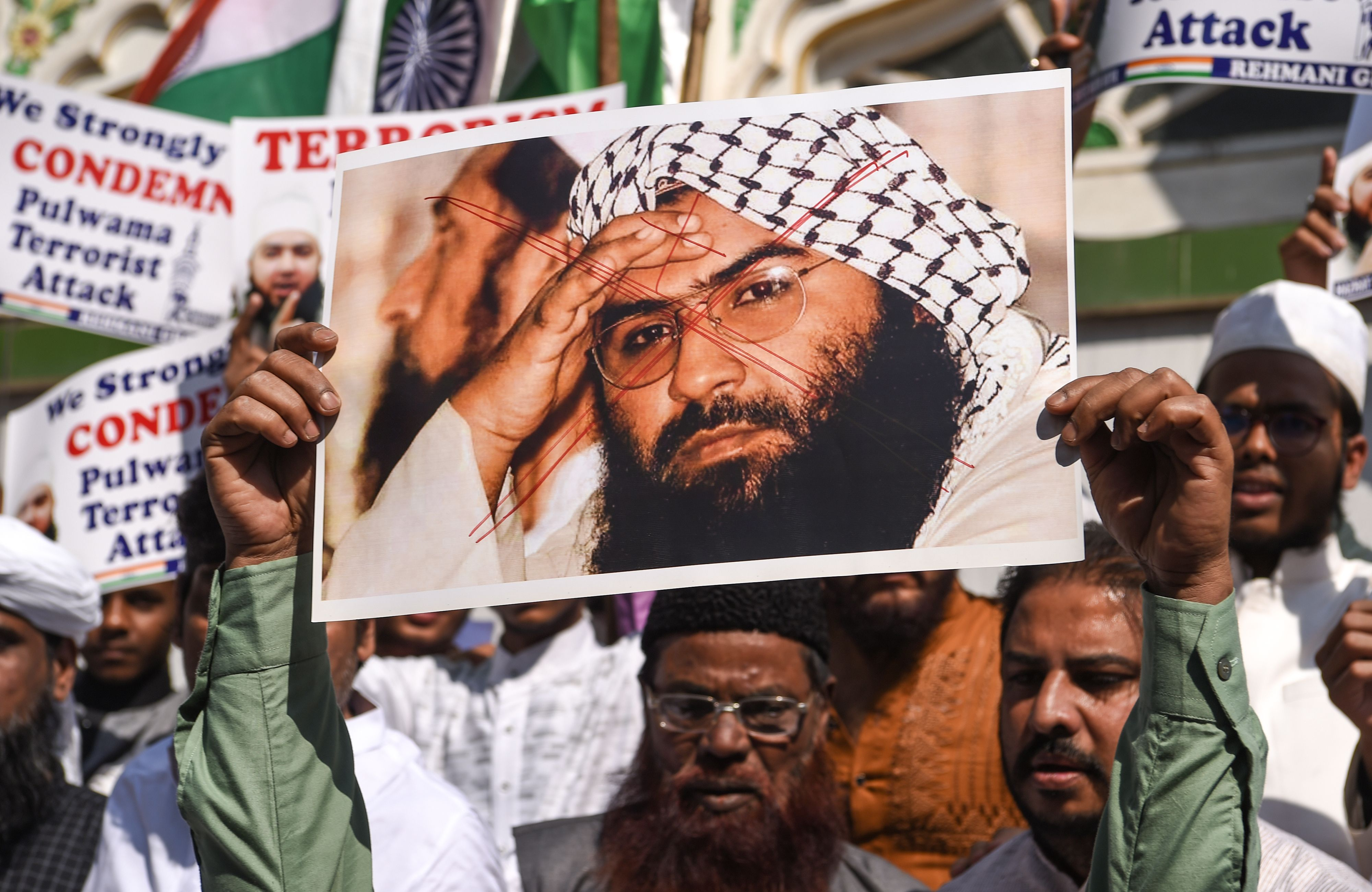 Indian Muslims hold a scratched photo of Jaish-e-Mohammad group chief, Maulana Masood Azhar. (Photo: INDRANIL MUKHERJEE/AFP/Getty Images)