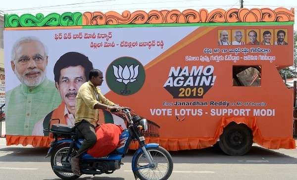 An Indian man rides a motorbike past an election campaign vehicle of the Bharatiya Janata Party (BJP) ahead of the forthcoming national elections in Hyderabad on March 27, 2019. - India is not just the world's biggest democracy, its elections are also the most gruelling -- with nearly six weeks between the first round of voting on April 11 and the last. (Photo by NOAH SEELAM / AFP)        (Photo credit should read NOAH SEELAM/AFP/Getty Images)