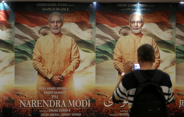 """A man uses his mobile phone to take photographs of a poster of the upcoming film """"PM Narendra Modi"""" during the launch of its poster in Mumbai, India January 7, 2019. (Photo: REUTERS/Francis Mascarenhas)"""