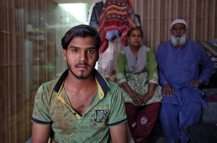 Mohammad Rafiq, 18, poses with his parents inside their house in Ahmedabad, India, April 17, 2019. Picture taken April 17, 2019. REUTERS/Ami