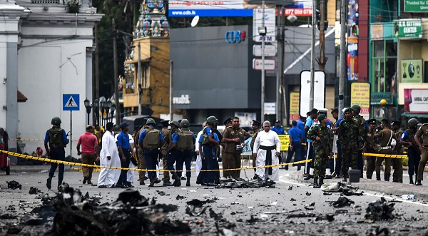 Sri Lankan security personnel inspect the debris of a car after it explodes when police tried to defuse a bomb near St. Anthony's Shrine as priests look on in Colombo on April 22, 2019, a day after the series of bomb blasts targeting churches and luxury hotels in Sri Lanka (Photo: JEWEL SAMAD/AFP/Getty Images).