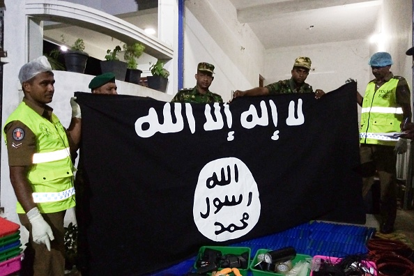 Security personnel display seized items after they raid what believed to be an Islamist safe house in the eastern town of Kalmunai.  (Photo by STRINGER / AFP/ Getty Images)