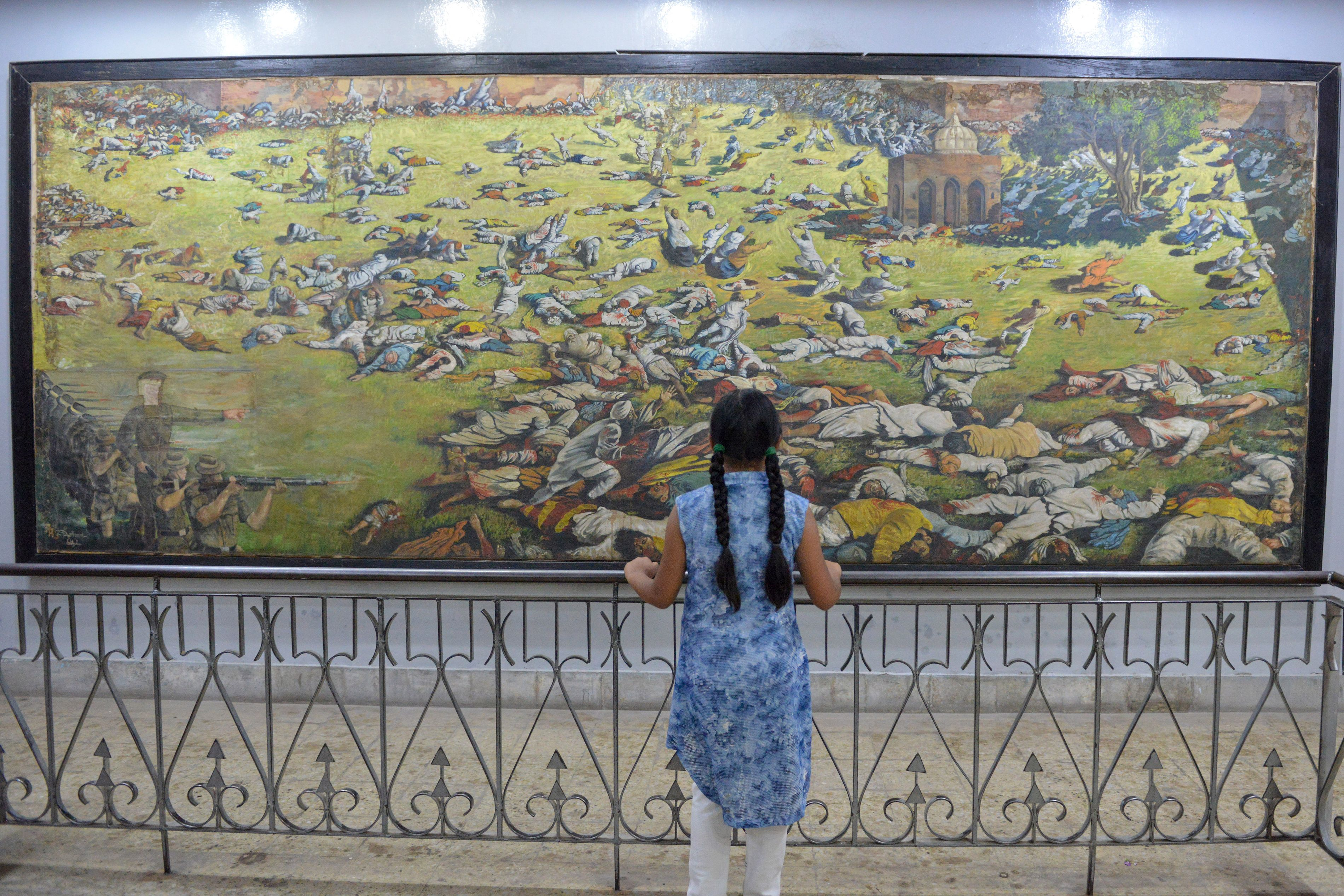 A visitor stands in front of a painting of martyrs last Sunday (7) ahead of the 100th anniversary of the massacre on Saturday (13) (Pic credit: NARINDER NANU/AFP/Getty Images)