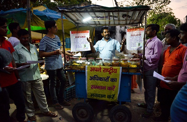 Indian bicycle-snack-hawker, Lal Mani Das, speaks to his customers and prospective voters to raise awareness on the country's election at a vegetable market in Patna (Photo: NARINDER NANU/AFP/Getty Images).