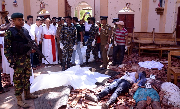 Sri Lankan soldiers and religious members of the parish look on inside the St Sebastian's Church at Katuwapitiya in Negombo on April 21, 2019, following a bomb blast during the Easter service that killed many (Photo: STR/AFP/Getty Images).