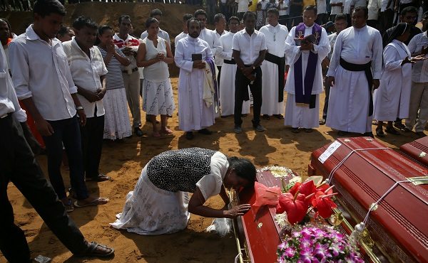 A woman reacts next to a coffin during a mass burial of victims, two days after a string of suicide bomb attacks on churches and luxury hotels across the island on Easter Sunday, at a cemetery near St. Sebastian Church in Negombo, Sri Lanka April 23, 2019 (Photo: REUTERS/Athit Perawongmetha).