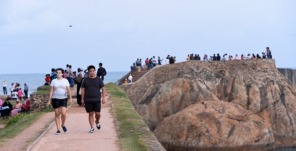Samaraweera said tourism was emerging as Sri Lanka's success story when Sunday's blast shattered hopes of reaching a revenue of $5bn, up from last year's $4.4bn (Photo: Tourists walk at Galle fort in Sri Lanka/ ISHARA S. KODIKARA/AFP/Getty Images).