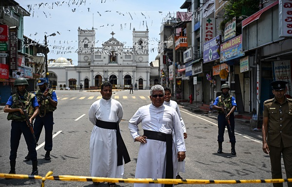 Priests walk on a blocked street as soldiers stand guard outside St. Anthony's Shrine in Colombo on April 25, 2019, following a series of bomb blasts targeting churches and luxury hotels on the Easter Sunday in Sri Lanka (Photo: JEWEL SAMAD/AFP/Getty Images).