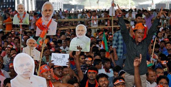 Supporters of India's ruling Bharatiya Janata Party react as they hold cut-outs of prime minister Narendra Modi during an election campaign rally addressed by Modi in Kolkata India, April 3, 2019 (Photo: REUTERS/Rupak De Chowdhuri).