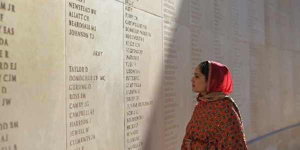 Punjabi folk band singer Amanroop Rahal views the names of the fallen after a Service of Remembrance to mark the Centenary of the World War One Battle of Neuve Chapelle at The National Memorial Arboretum in Alrewas, England