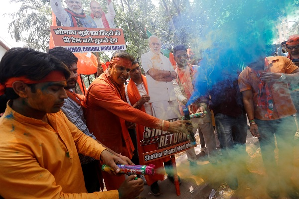 BJP supporters celebrate after learning the initial election results outside the party headquarters in New Delhi. (Photo: REUTERS/Adnan Abidi)