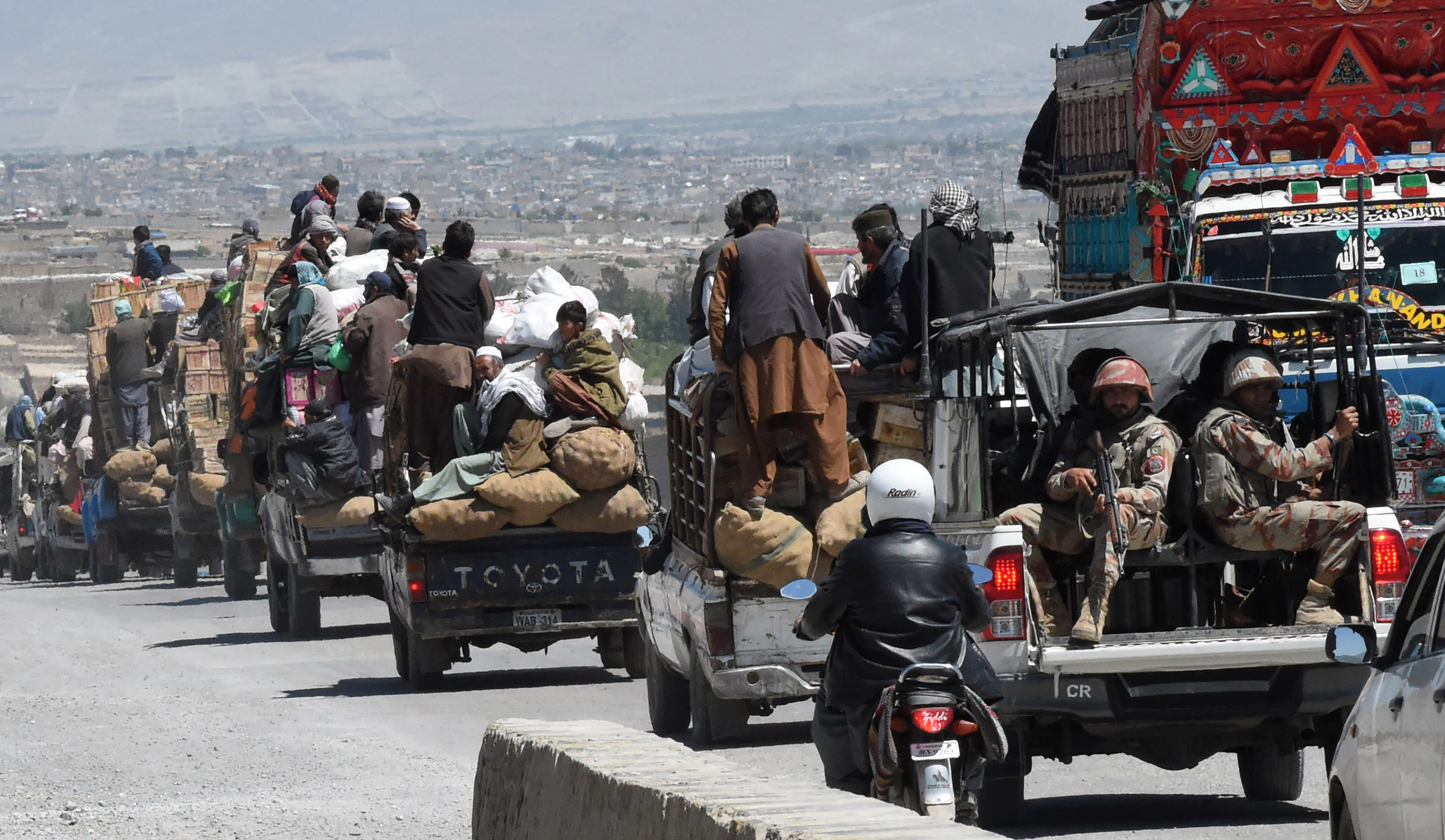 Pakistani paramilitary soldiers escort vehicles carrying Shiite Hazara minority traders and their fruit and vegetables on the way back from a market to a heavily guarded enclave where they live on the outskirts of Quetta.  (Photo by BANARAS KHAN/AFP/Getty Images)