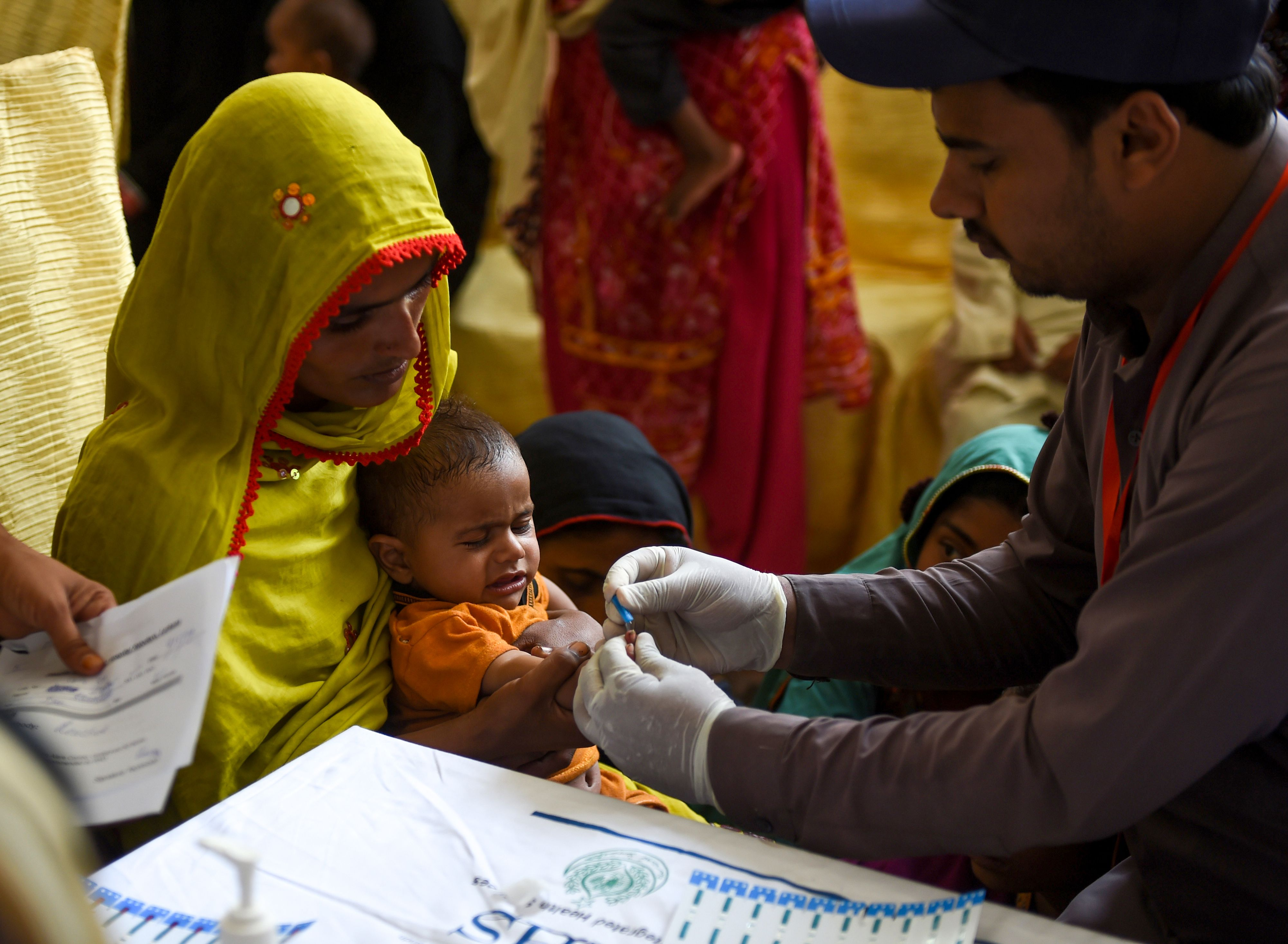 In this image taken on May 9, 2019, a Pakistani paramedic takes a blood sample from a baby for a HIV test at a state-run hospital in Rato Dero in the district of Larkana of the southern Sindh province. - Parents nervously watch over their children as they jostle in line to be tested for HIV in a village near Pakistans Larkana amid a sudden outbreak among its young who have allegedly been infected by a doctor using a contaminated syringe. (Photo by RIZWAN TABASSUM / AFP) / TO GO WITH: Pakistan-health-HIV-children, SCENE by Ashraf KHAN        (RIZWAN TABASSUM/AFP/Getty Images)