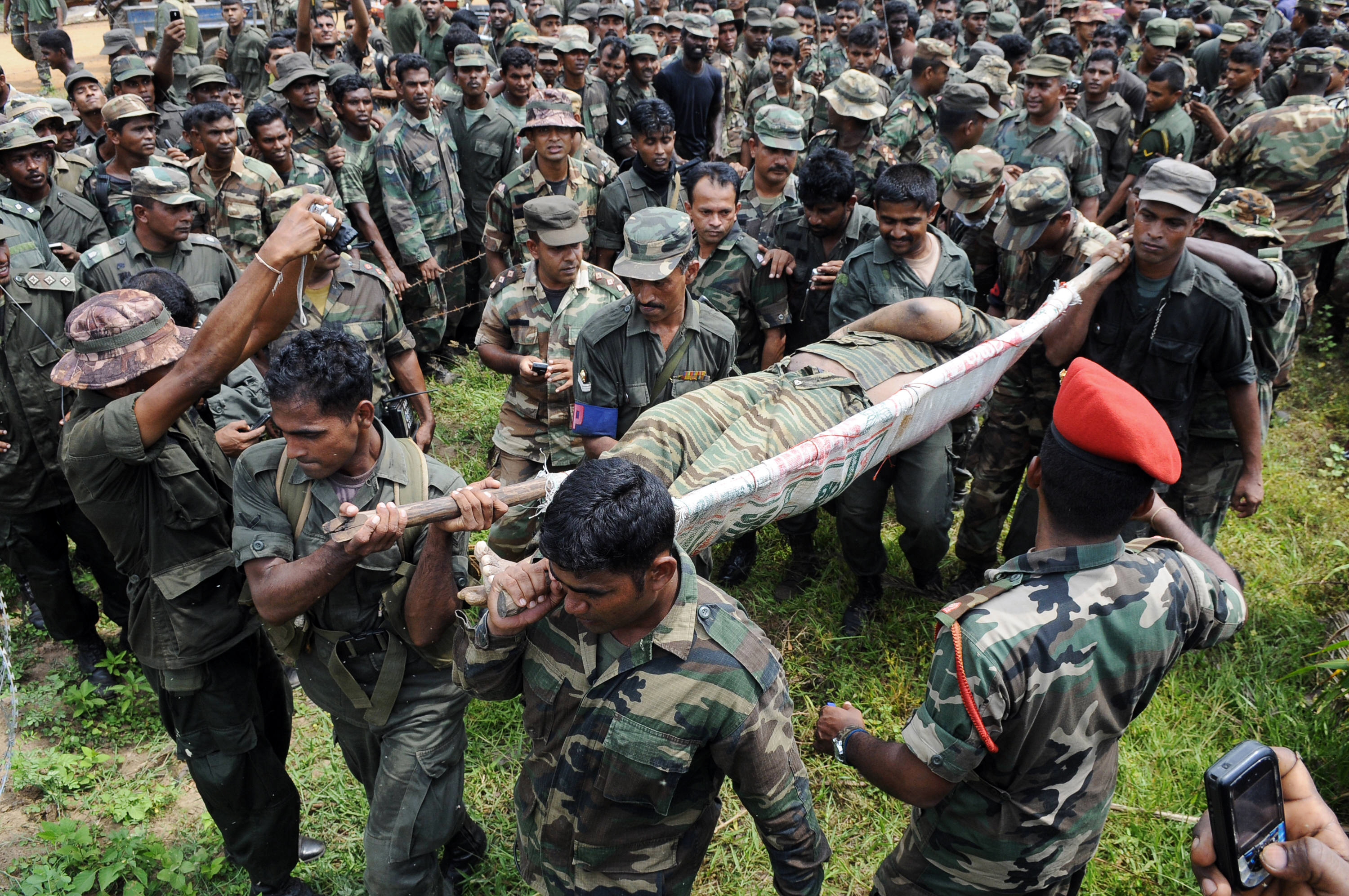 CORRECTING SOURCE Sri Lankan soldiers carry the remains of what is said to be Tamil Tiger rebel leader Velupillai Prabhakaran in the district of Mullaittivu on May 19, 2009. Sri Lanka marked victory over Tamil Tiger rebels with a national holiday, though security forces were on a state of high alert against revenge attacks after the entire rebel leadership was wiped out in a final stand. AFP PHOTO/Associated Newspapers of Ceylon Limited (Lake House) (Photo credit should read STR/AFP/Getty Images)