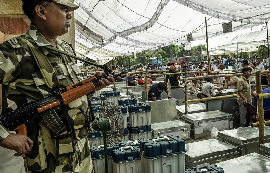 Indian CISF soldier guards elections voting machines at an Elections Commission facility while the distribution of voting machines go to polling stations on April 10, 2019 in Noida, India (Photo: Atul Loke/ Getty Images).