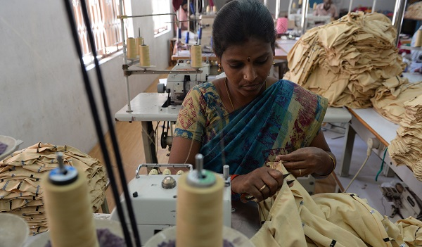 """In this photo taken on March 25, 2019, Indian labourer Jothi stitches apparel at the tailoring section of a production unit in the south Indian city of Tiruppur. - India's Prime Minister Narendra Modi announced the surprise withdrawal of most of the country's currency from circulation in November 2016, justifying the sudden move as a means to flush out cash being hoarded by wealthy tax cheats. But ordinary businesses reliant on cash were kneecapped, banks thrown into chaos and the entire Indian economy recoiled from what one global lender described as an """"acute monetary shock"""". (Photo by Arun SANKAR / AFP) / TO GO WITH  India-economy-vote, FOCUS by Bhuvan BAGGA        (Photo credit should read ARUN SANKAR/AFP/Getty Images)"""