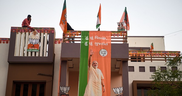 Indian residents put up Bharatiya Janata Party (BJP) flags and posters of prime minister Narendra Modi on their house in Ahmedabad. (Photo: PUNIT PARANJPE/AFP/Getty Images).