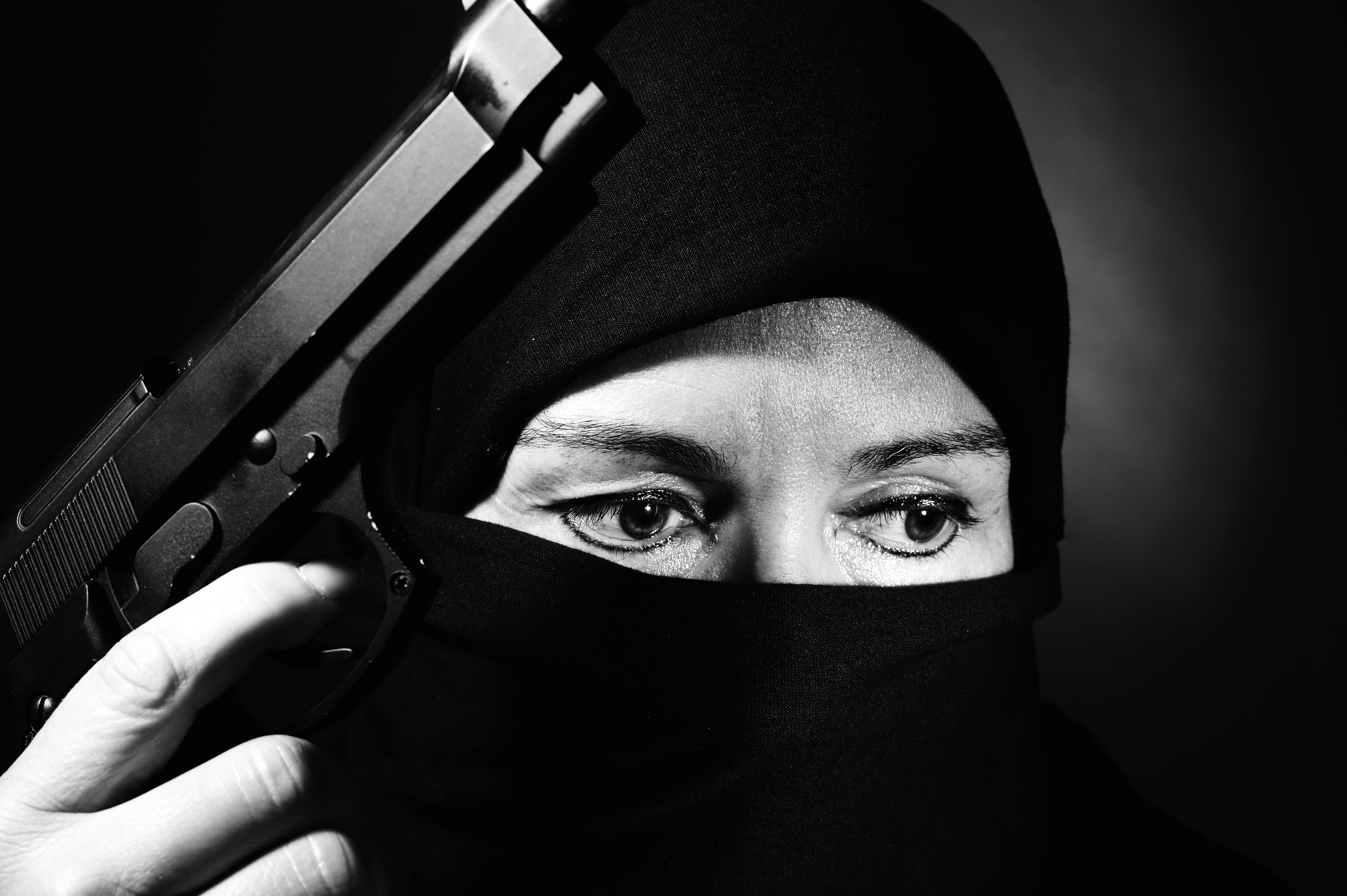 close-up of veiled middle eastern woman  with gun