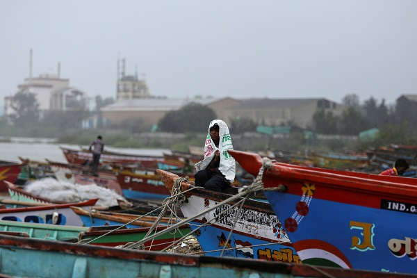 A boy covers himself from rain as he sits on a fishing boat along the shore ahead of Cyclone Vayu in Veraval, India, June 13, 2019. (Photo: REUTERS/Amit Dave)