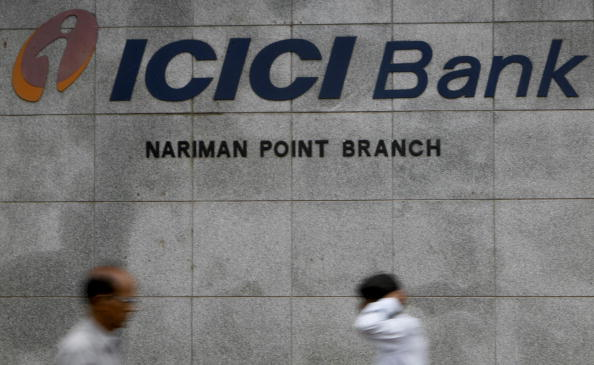 FILE PHOTO: Pedestrians walk outside the ICICI bank in Mumbai. (Photo: PAL PILLAI/AFP/Getty Images)
