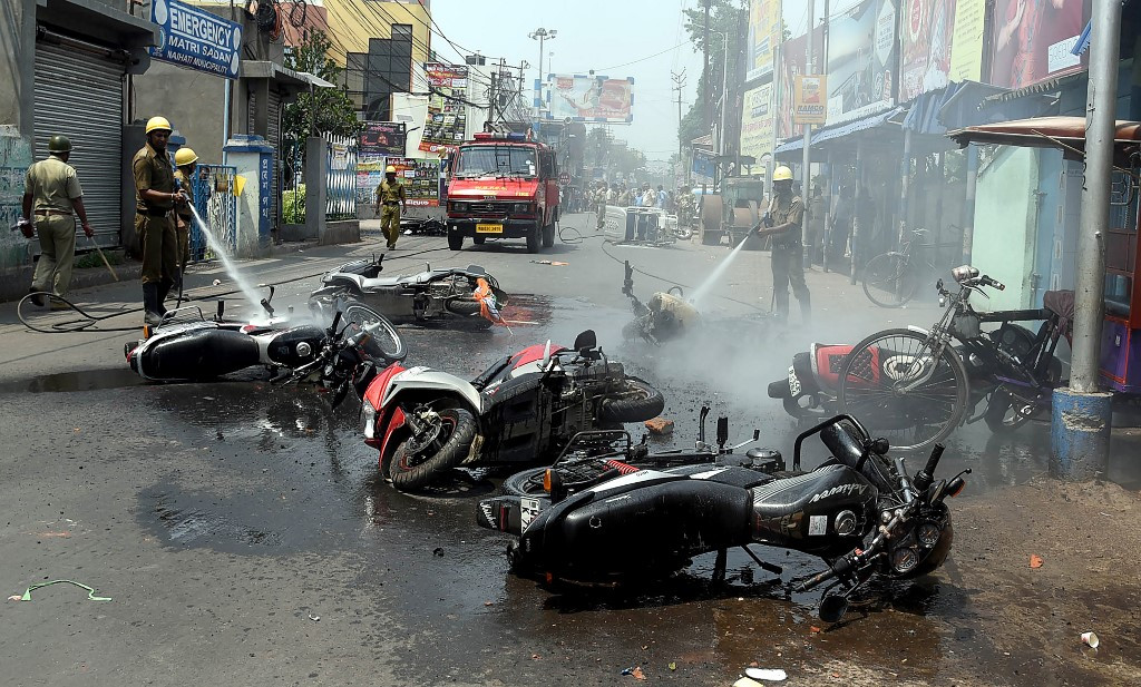 Indian firemen douse burned vehicles after clashes between Trinamool Congress (TMC) and Bharatiya Janata Party (BJP) workers in Naihati, West Bengal. Violent clashes continued in India on May 26 between supporters of Prime Minister Narendra Modi's Hindu nationalist party and a regional party in the politically volatile eastern state of West Bengal, officials said. (AFP)
