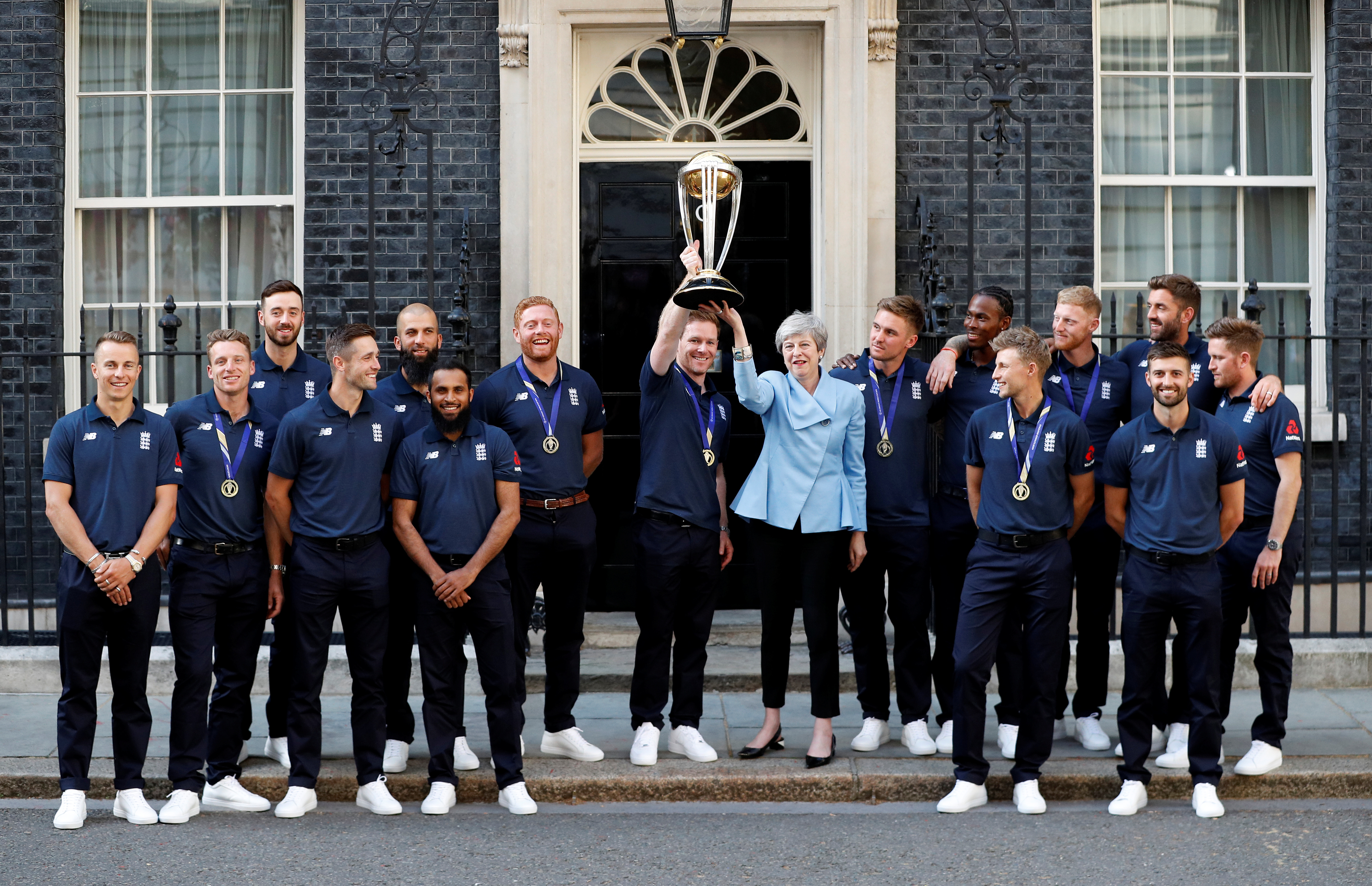 Cricket - The England cricket team meet Theresa May - Downing Street, London, Britain - July 15, 2019   England's Eoin Morgan and Britain's Prime Minister Theresa May lift the trophy as they pose with the team outside number 10   REUTERS/Peter Nicholls