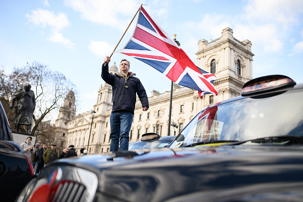 A taxi driver waves a Union flag as he stands on his cab in the middle of a static protest in Parliament Square on February 11, 2019 in London, England. The Independent Workers Union of Great Britain's United Private Hire drivers have gathered outside the Transport for London headquarters protesting at the introduction of congestion charges for minicabs. (Photo by Leon Neal/Getty Images)