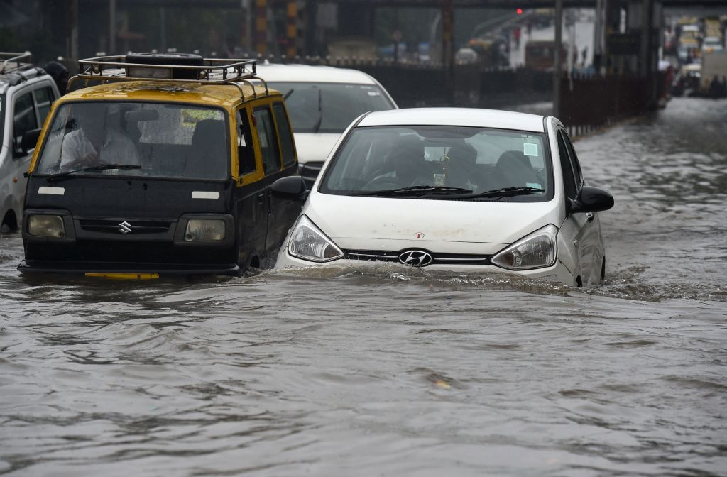 Vehicles drive along a flooded street after heavy rain showers in Mumbai on July 1, 2019. (Photo: PUNIT PARANJPE/AFP/Getty Images)