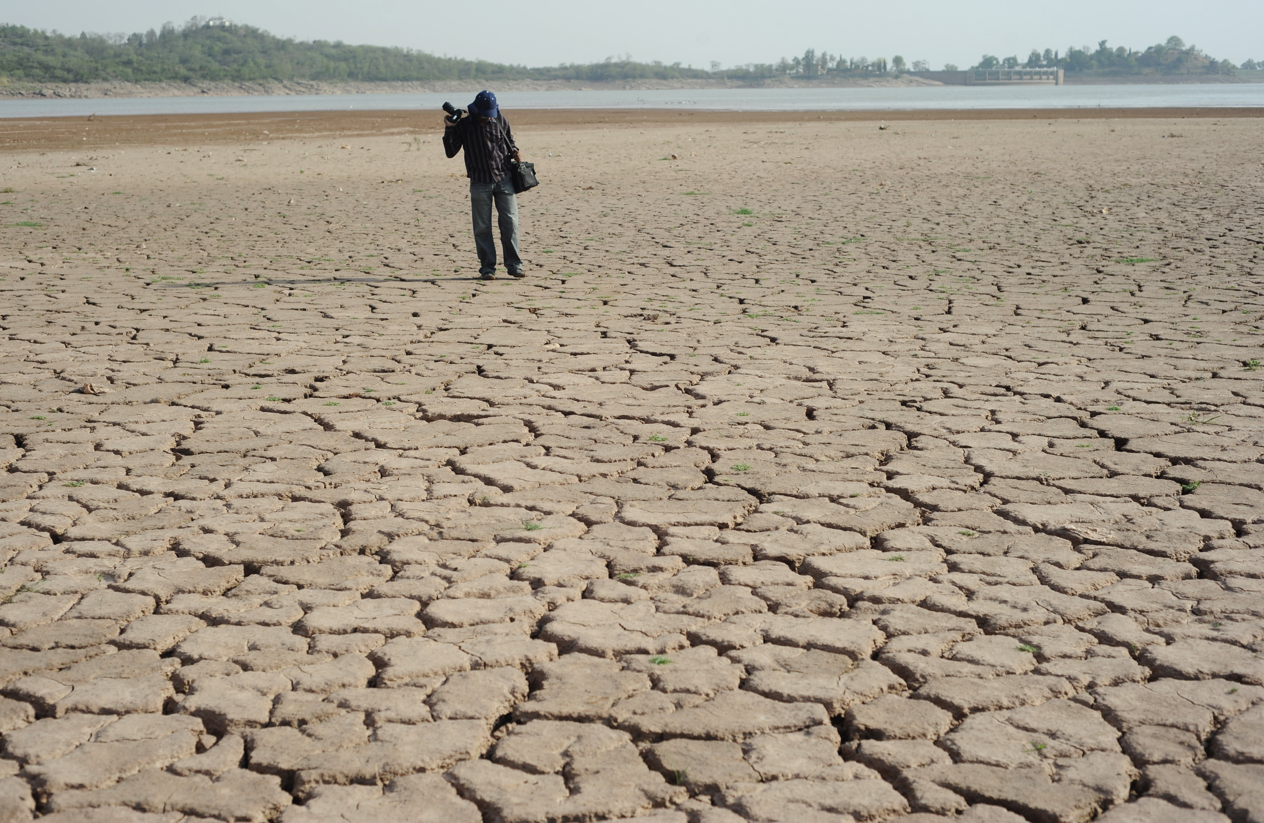 """A Pakistani photographer takes pictures of a dry portion of the Rawal Dam in Islamabad on June 22, 2010. The federal capital is facing a severe water shortage due to a drought. Pakistan is facing a """"raging"""" water crisis that if managed poorly could mean Pakistan would run out of water in several decades, experts say, leading to mass starvation and possibly war, a  newspaper reports said.  AFP PHOTO/Farooq NAEEM (Photo credit should read FAROOQ NAEEM/AFP/Getty Images)"""