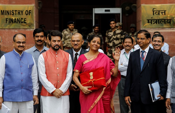 India's Finance Minister Nirmala Sitharaman (C) gestures during a photo opportunity as she leaves her office to present the federal budget in the parliament in New Delhi, India, July 5, 2019 (Photo: REUTERS/Anushree Fadnavis).