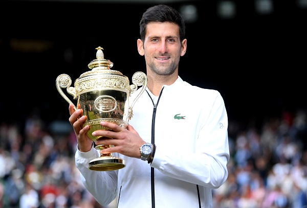 Novak Djokovic poses with the trophy as he celebrates winning the final against Switzerland's Roger Federer (Laurence Griffiths/Pool via REUTERS).