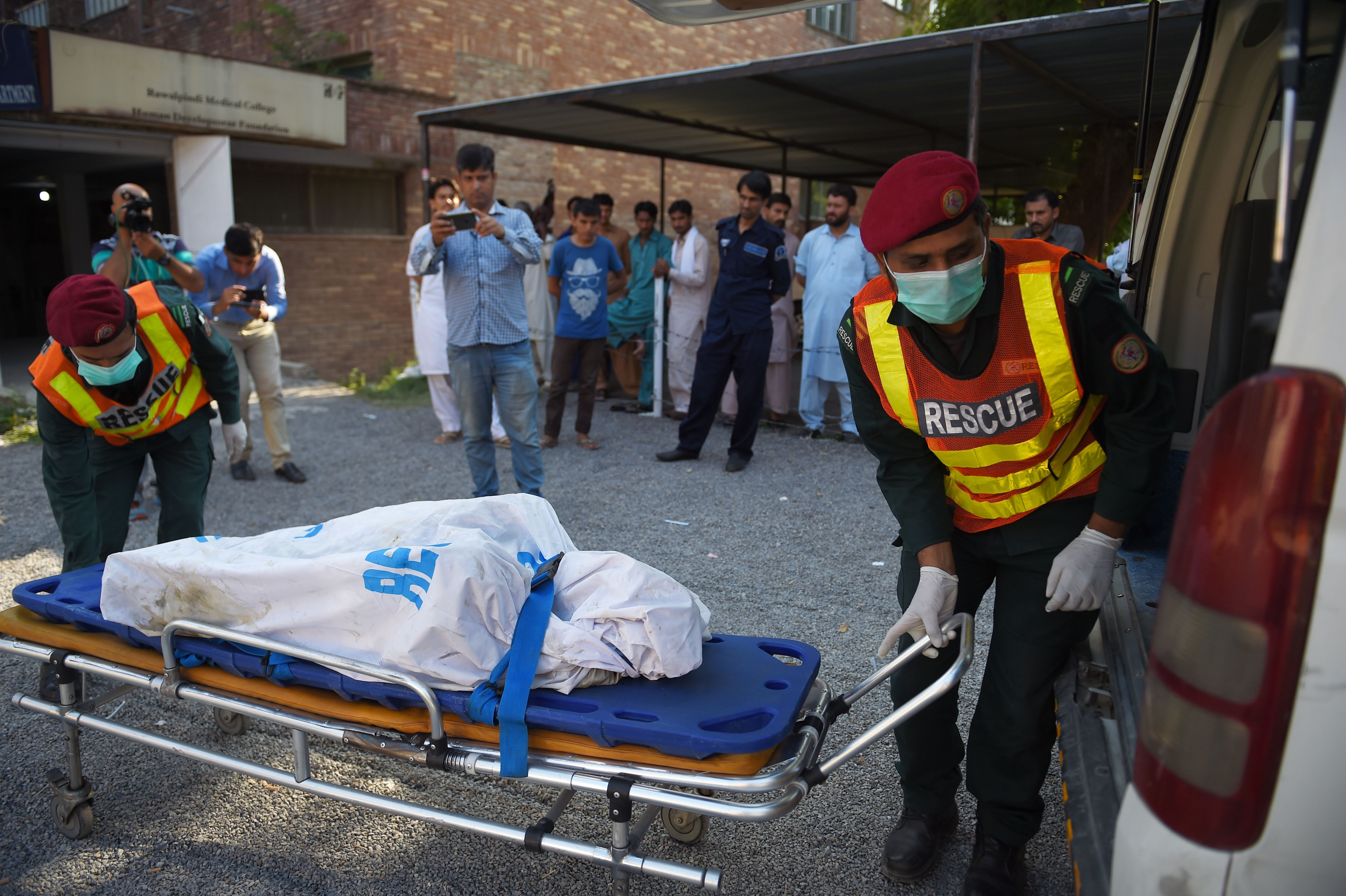 The body of a victim, killed after a Pakistani Army Aviation Corps aircraft crashed into a residential area, is wheeled to a waiting ambulance at a hospital to be taken for DNA identification in Rawalpindi on July 30, 2019 (Pic credit: FAROOQ NAEEM/AFP/Getty Images)