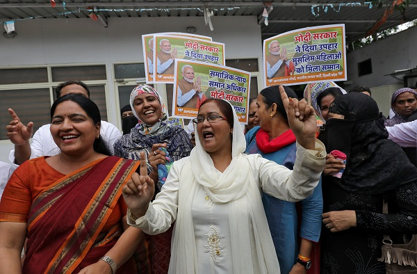 "Muslim women along with supporters of India's ruling Bharatiya Janata Party (BJP) celebrate after India's parliament approved a bill on Tuesday (30) outlawing the centuries-old right of a Muslim man to instantly divorce his wife, in New Delhi, India, July 31, 2019. The placards read: ""Gift from Modi government, honour to Muslim women"" (REUTERS/Anushree Fadnavis)."