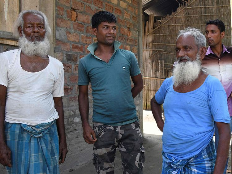 Mohammed Rehat Ali (R), 71, one of many to fall foul of a citizenship process in the north-eastern Indian state of Assam, stands next to relatives at Khopnikuchi village in Assam's Kamrup district. Image Credit: AFP