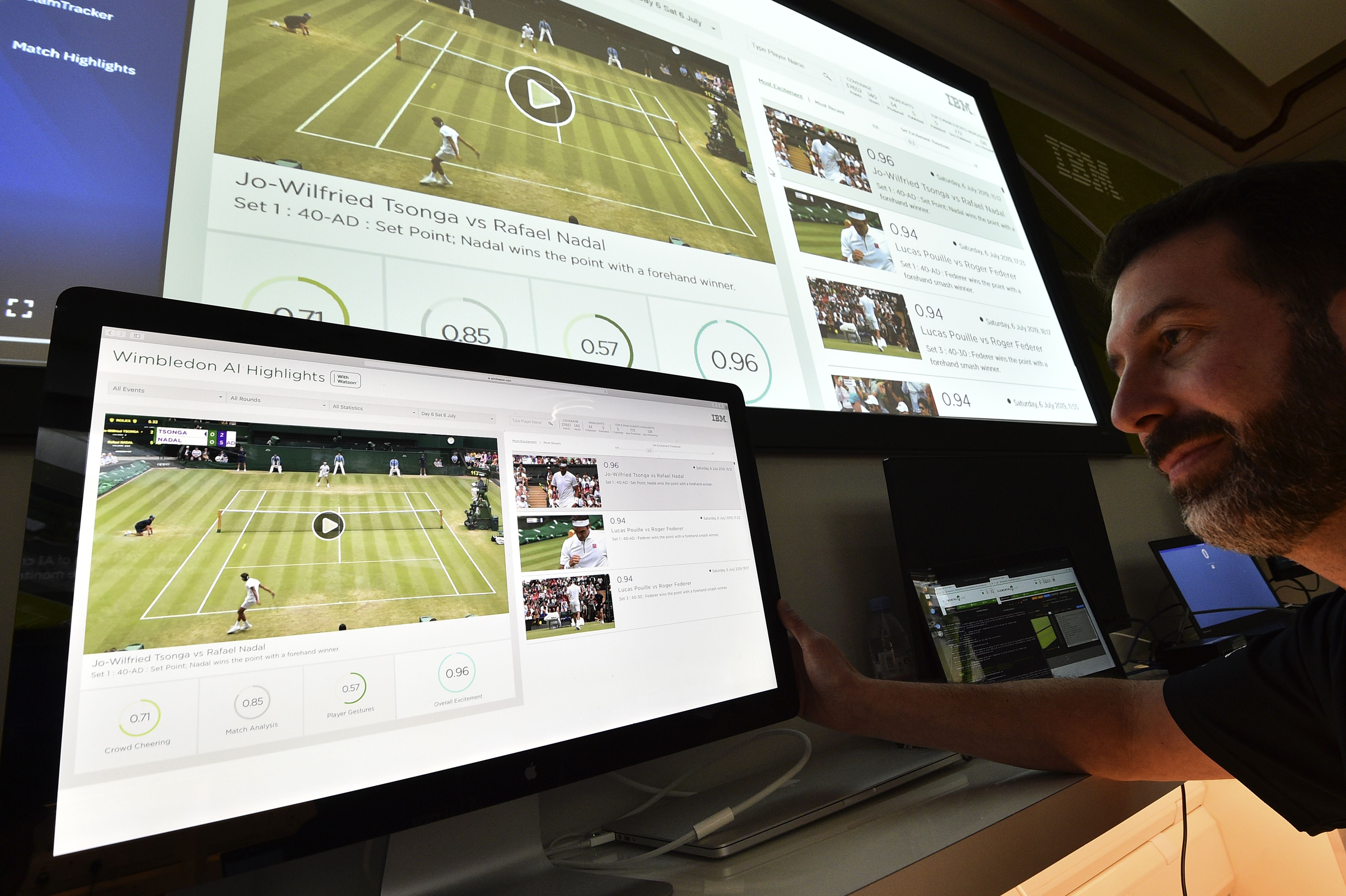An IBM technician poses with screens showing IBM's AI-generated highlights of play on the sixth day of the 2019 Wimbledon Championship.