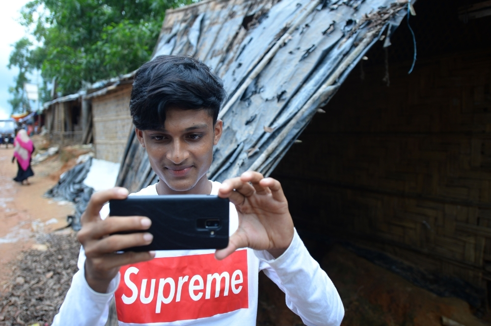 In this picture taken on July 23, 2019, Rohingya youth Mohammad Rafiq uses his mobile phone to take photos at the Kutupalong refugee camp. -AFP