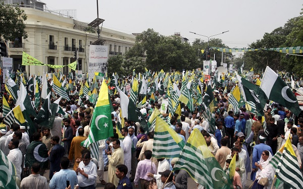 People carrying flags of Pakistan and Azad Kashmir, pray during a countrywide 'Kashmir Hour' demonstration to express solidarity with the people of Kashmir, observing a call by Prime Minister Imran Khan in Lahore, Pakistan August 30, 2019 (REUTERS/Mohsin Raza).