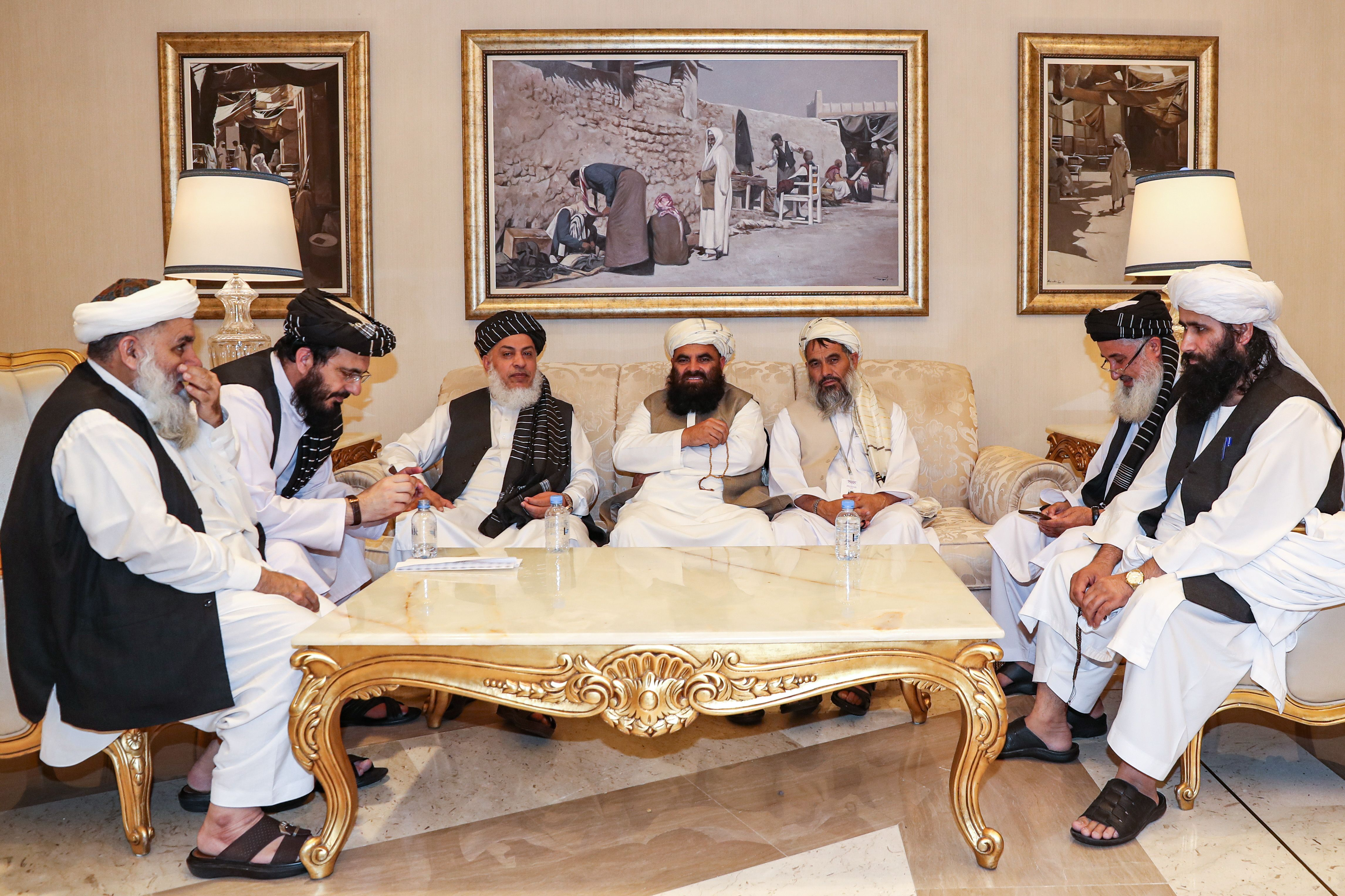 Mohammad Nabi Omari (2nd-L), a Taliban member formerly held by the US at Guantanamo Bay and reportedly released in 2014 in a prisoner exchange, and Taliban negotiator Abbas Stanikzai (3rd-L) sit with other Taliban members during the second day of the Intra Afghan Dialogue talks in the Qatari capital Doha on July 8, 2019. . (JAAFAR/AFP/Getty Images)