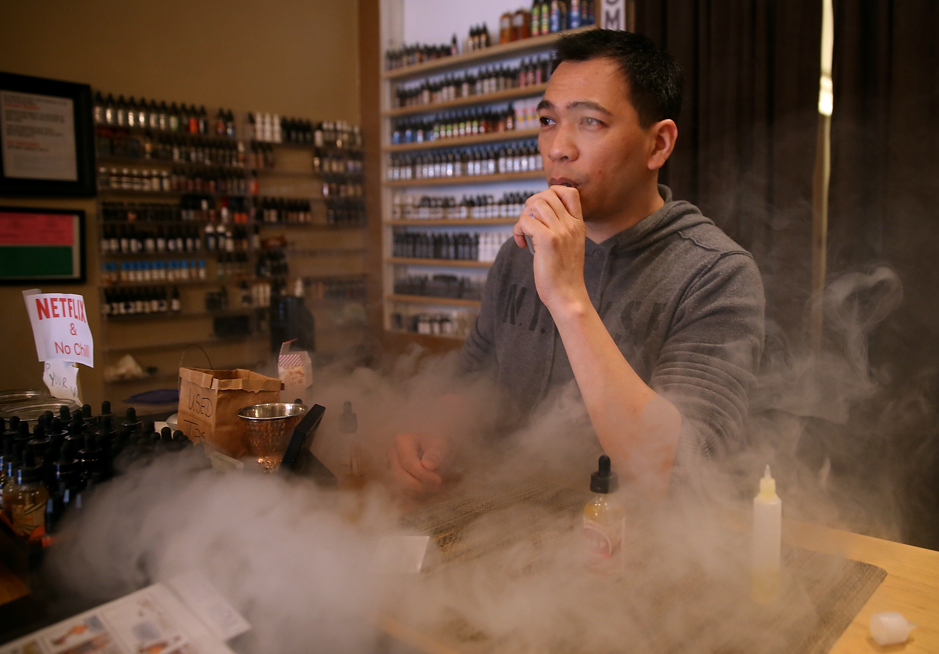 SAN FRANCISCO, CA - MAY 05:  Christopher Chin blows puffs on an e-cigarette as he waits for customers at Gone With the Smoke Vapor Lounge on May 5, 2016 in San Francisco, California. The U.S. Food and Drug Administration announced new federal regulations on electronic cigarettes that will be the same as traditional tobacco cigarettes and chewing tobacco.  (Photo by Justin Sullivan/Getty Images)