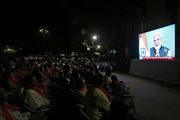 People watch as prime minister Narendra Modi delivers an address to the nation, on a TV screen in Ahmedabad, India, August 8, 2019 (REUTERS/Amit Dave).