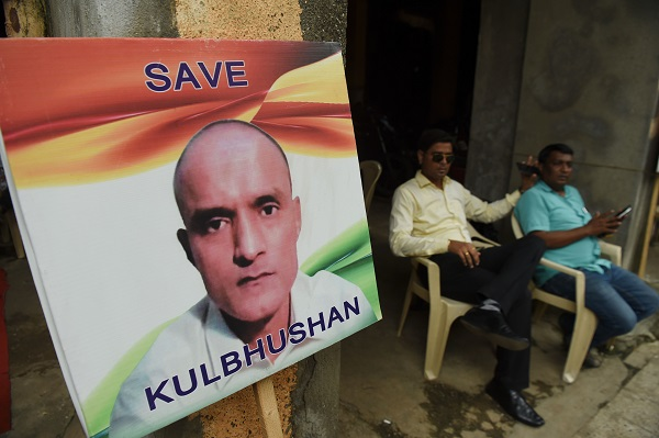 Indian residents sit next to a placard with the picture of Kulbhushan Jadhav (Photo: INDRANIL MUKHERJEE/AFP/Getty Images).