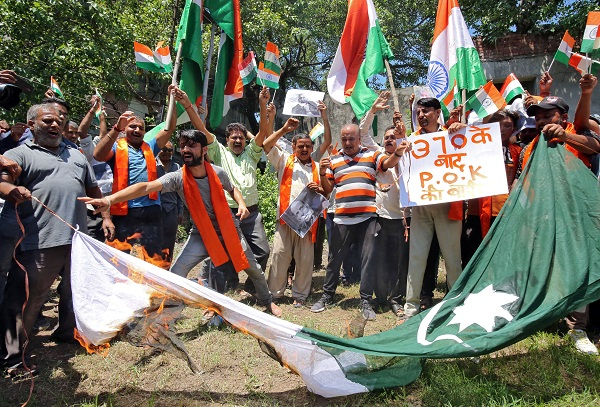 Supporters of Shiv Sena, a Hindu hardline group, burn a flag resembling Pakistan's national flag during a protest, after Pakistan said it would expel India's ambassador and suspend bilateral trade with India, following the scrapping of the special constitutional status for Kashmir by the Indian government, in Jammu August 8, 2019 (REUTERS/Mukesh Gupta).