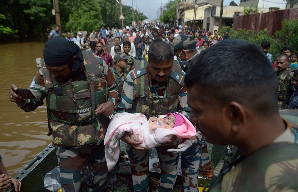 An Army soldier carries an infant as they evacuate flood-affected people to a safer place in Sangli district in the western state of Maharashtra, India, August 11, 2019 (REUTERS/Stringer).