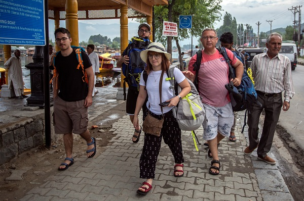 Foreign tourists carry their luggage as they walk on the banks of Dal Lake before leaving Srinagar August 3, 2019 (REUTERS/Stringer).