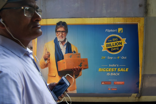 In this photograph taken on September 26, 2019, a commuter looks on as a train with advertisements of the upcoming festive sale of an online e-commerce portal featuring Bollywood actor Amitabh Bachchan passes by in Mumbai (Photo: INDRANIL MUKHERJEE/AFP/Getty Images).