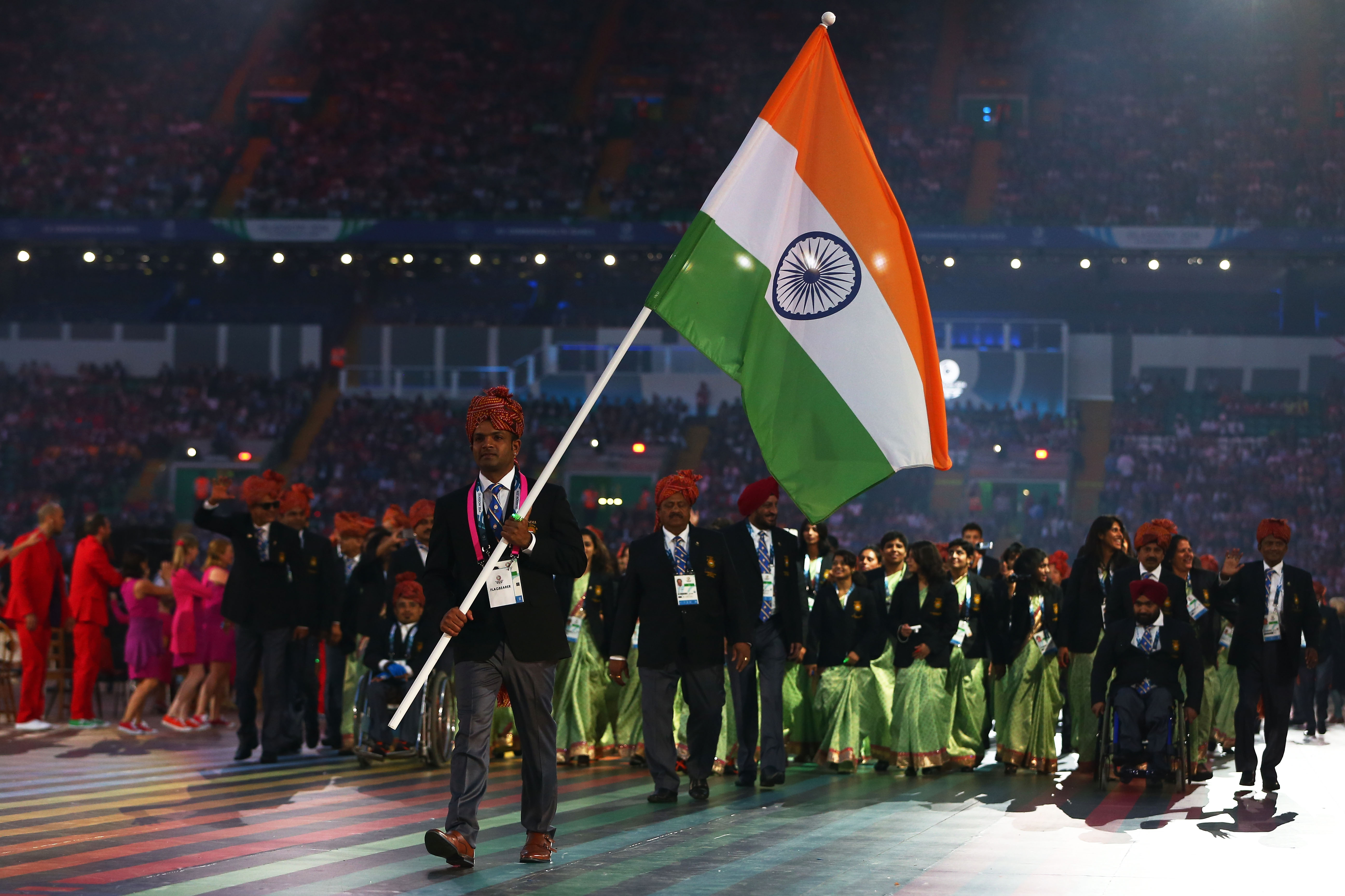 Flag bearer and Shooter Vijay Kumar of India leads the team during the Opening Ceremony for the Glasgow 2014 Commonwealth Games at Celtic Park on July 23, 2014 in Glasgow, Scotland.  (Photo by Quinn Rooney/Getty Images)
