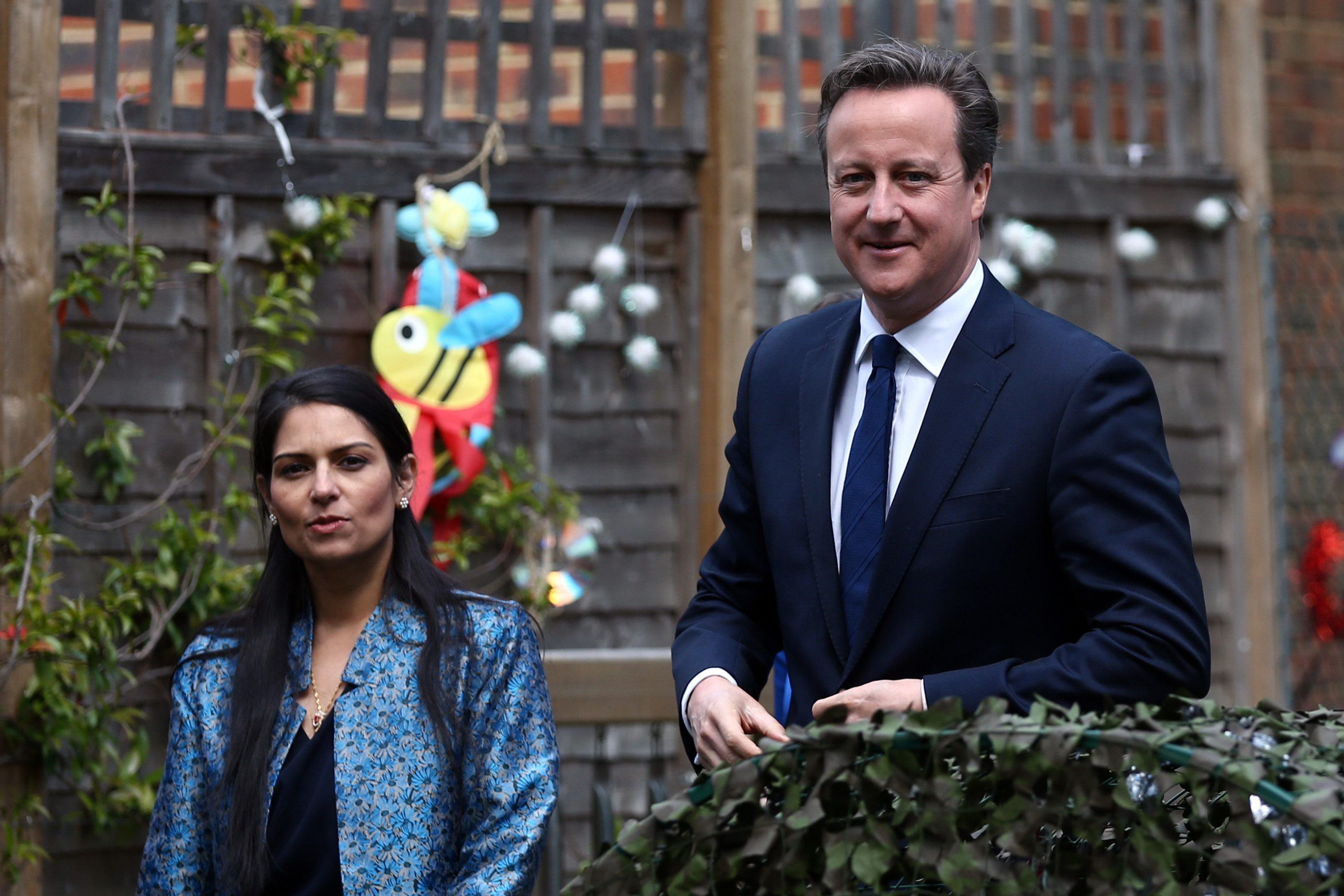 David Cameron (R) walks with Priti Patel during a visit to a children's nursery on June 1, 2015. (Photo by Carl Court - WPA Pool / Getty Images)
